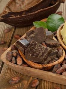 шоколад с эквивалентом масла какао в деревянной пиале на деревянном подносе с зернами какао бобов